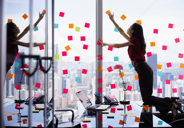 Busy Person Attaching Many Sticky Notes On Large Window Stock photo © diego_cervo