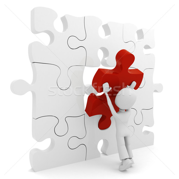 Stock photo: 3d man pushing a puzzle piece into its place