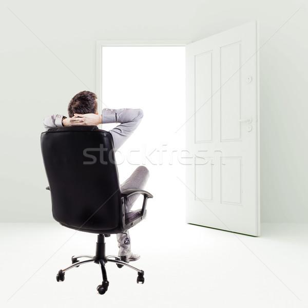 Business man in a chair in front of open door Stock photo © digitalgenetics