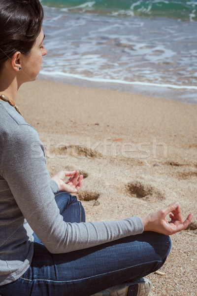 Body detail of a beautiful girl in a meditation on the beach Stock photo © digoarpi