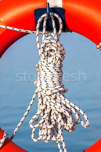 Orange life buoy with rope Stock photo © digoarpi