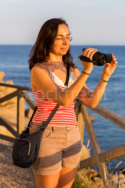 Pretty girl shooting a movie with camcorder Stock photo © digoarpi