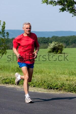 Senior corredor treinamento competição céu grama Foto stock © digoarpi