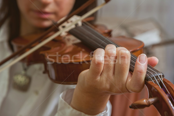 Symphony orchestra on stage, hands playing violin. Shallow depth Stock photo © digoarpi