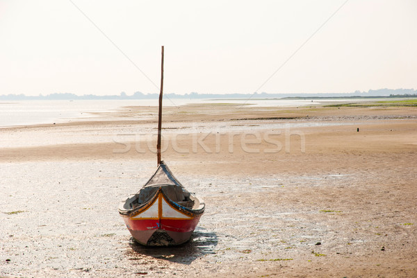Fishing boat on the beach in low tide Stock photo © dinozzaver