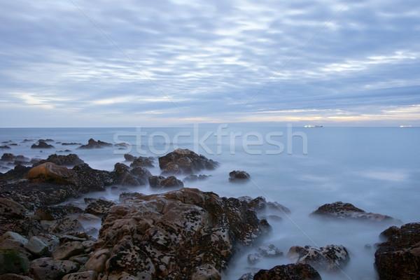 Longa exposição mar rochas noite crepúsculo céu Foto stock © dinozzaver