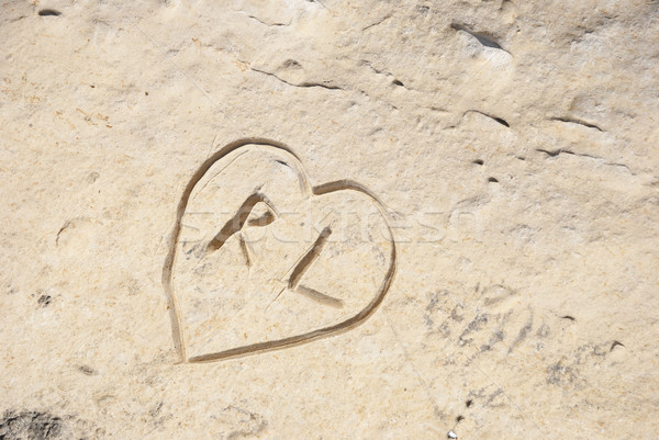 Carved initials with heart in the stone Stock photo © dinozzaver
