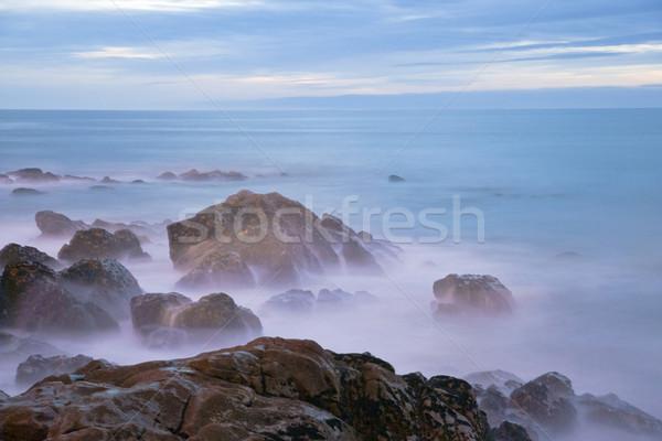 La exposición a largo mar rocas crepúsculo cielo Foto stock © dinozzaver