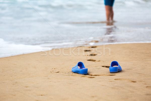 Beach Slippers and Blurred Silhouette of a Woman in Waves  Stock photo © Discovod