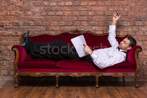 Businessman lying on a settee and reading paperwork Stock photo © Discovod
