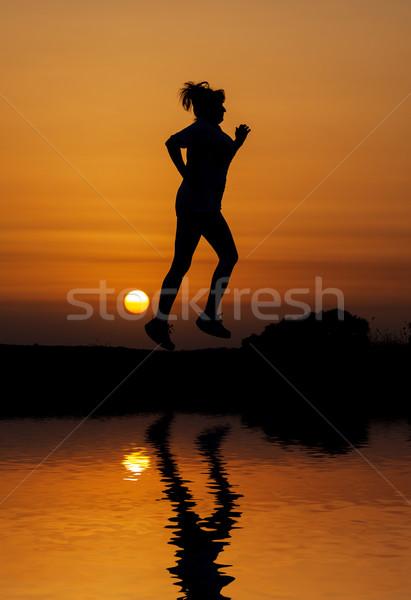 Silhouet vrouw lopen oranje zonsondergang reflectie Stockfoto © Discovod