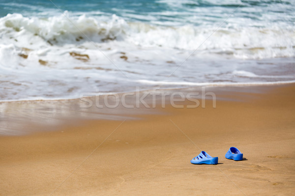 Women's Blue Slippers on a Sandy Ocean Beach Stock photo © Discovod