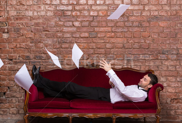 Businessman lying on a settee with flying papers Stock photo © Discovod