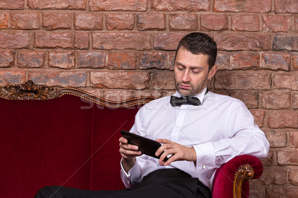 Businessman lying on a settee and reading tablet Stock photo © Discovod
