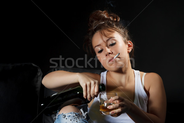Woman smoking while pouring a drink Stock photo © Discovod