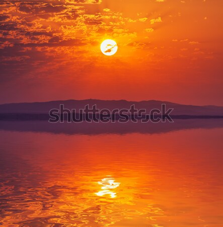 Vibrant rising sun at dawn over water Stock photo © Discovod