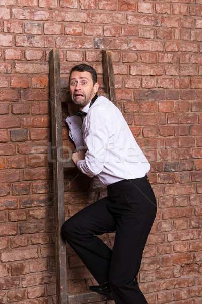 Terrified man trapped at the top of a ladder Stock photo © Discovod