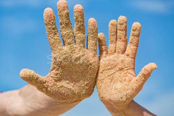 Nő férfi nyitva kezek fedett tengerparti homok Stock fotó © Discovod
