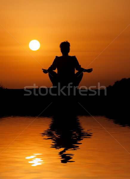 Silhouette woman sitting and relaxing against orange sunset Stock photo © Discovod