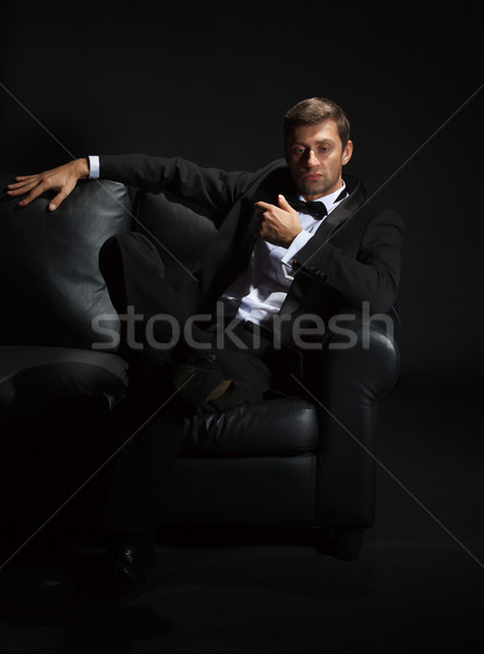 Handsome man in a tuxedo on couch Stock photo © Discovod