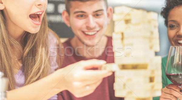 Group of young friends having fun playing board game at home - D Stock photo © DisobeyArt