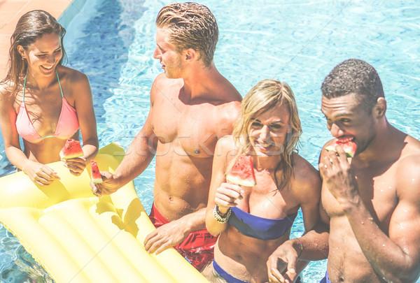 Mutlu arkadaşlar yeme karpuz yüzme havuzu otel Stok fotoğraf © DisobeyArt