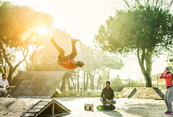 Breakdancer permorming a stunt jump in skate park outdoor - Youn Stock photo © DisobeyArt