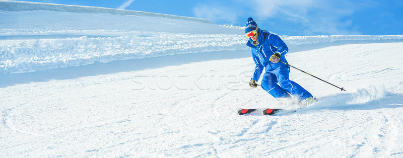 Young athlete skiing in alps mountains on sunny day - Skier ridi Stock photo © DisobeyArt