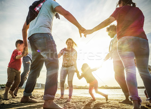 Diverse culture families playing with children on the beach - So Stock photo © DisobeyArt