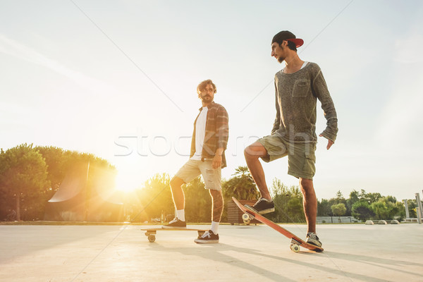 Young people training with longboard with back sun light- Skater Stock photo © DisobeyArt