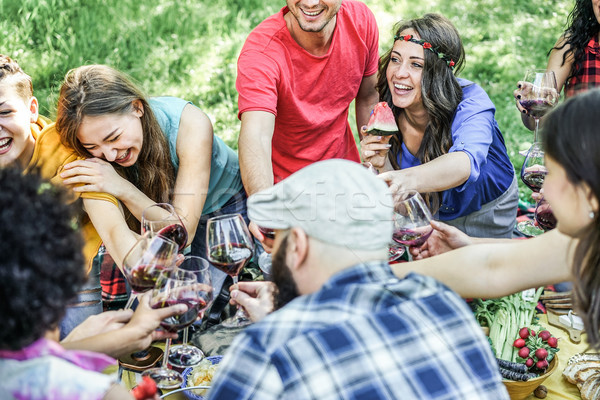 Group of happy friends cheering with glasses of red wine and eat Stock photo © DisobeyArt