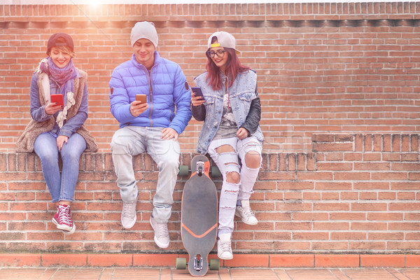 Group of young friends playing online with smartphones outdoor - Stock photo © DisobeyArt