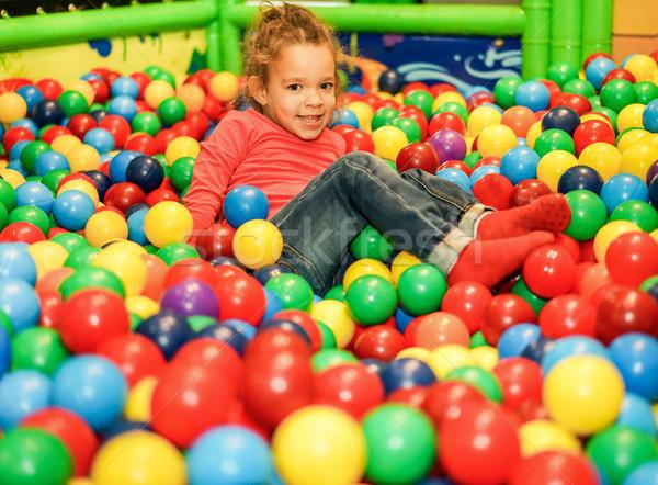 Cheerful child playing inside ball pit swimming pool - Little gi Stock photo © DisobeyArt