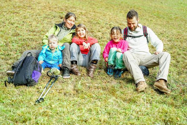 Happy traveler family sitting on grass doing trekking in switzer Stock photo © DisobeyArt