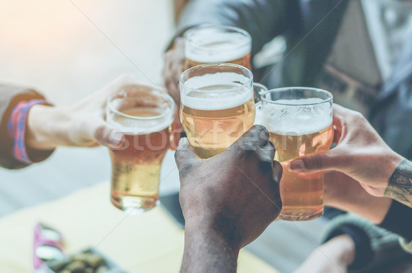 Multiracial group of friends enjoying a beer - Young people hand Stock photo © DisobeyArt
