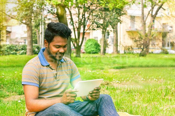Young indian man having video call on tablet in park university  Stock photo © DisobeyArt