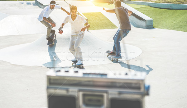 Stock photo: Young skaters performing with skateboard and listening music in
