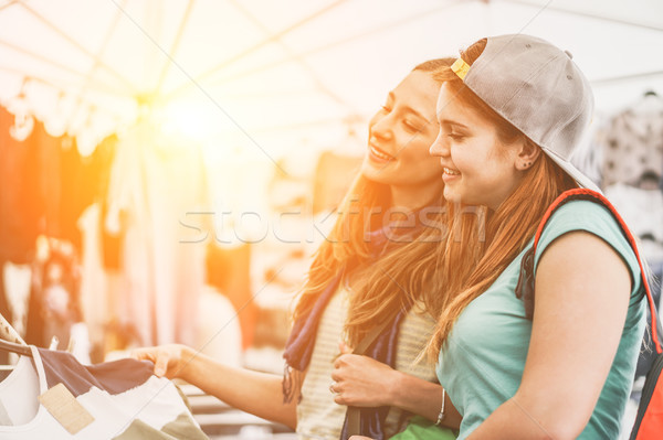 Young women doing shopping at the weekly cloth market at sunset  Stock photo © DisobeyArt
