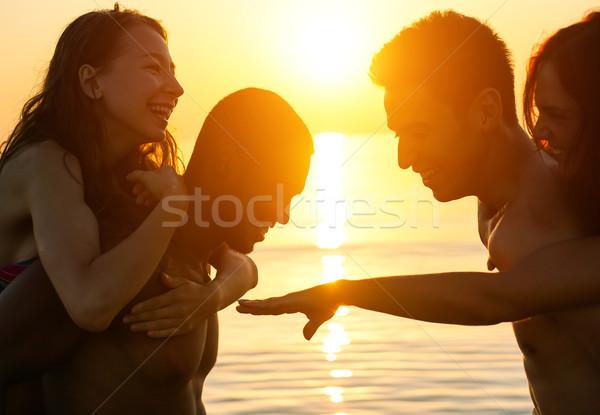 Silhouette gruppo amici nuoto spiaggia sunrise Foto d'archivio © DisobeyArt