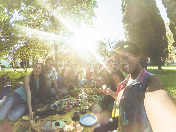 Stock photo: Happy mixed race woman taking selfie at picnic outdoor with her