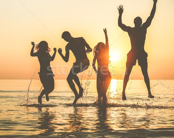 Silhouetten gelukkig vrienden springen binnenkant water Stockfoto © DisobeyArt