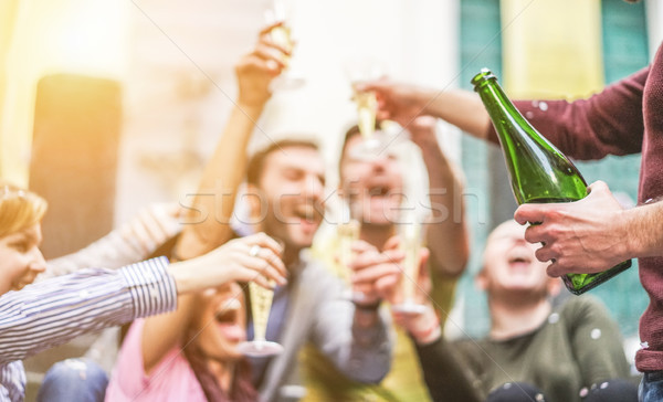 Happy friends celebrating drinking champagne and making party ou Stock photo © DisobeyArt