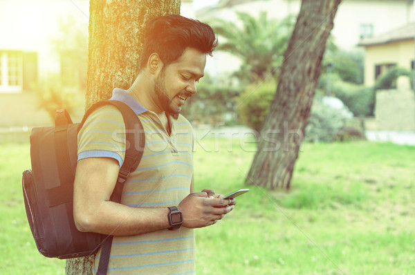 Portrait of a young Indian man texting in park residential conte Stock photo © DisobeyArt