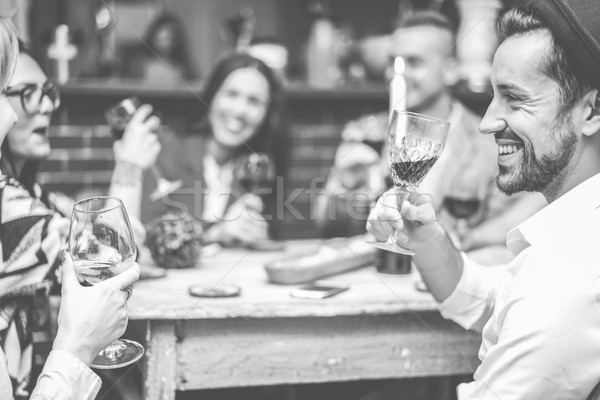 Happy fashion friends toasting wine in trendy cocktail bar resta Stock photo © DisobeyArt