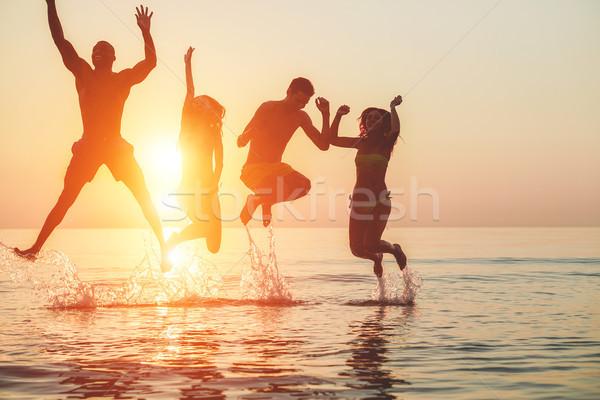 Sylwetki młodych znajomych wody plaży Zdjęcia stock © DisobeyArt