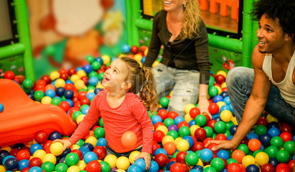 Diverse culture parents playing with their daughter inside ball  Stock photo © DisobeyArt