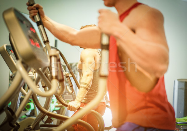 Fitness men using eliptical cross trainer in gym american club - Stock photo © DisobeyArt