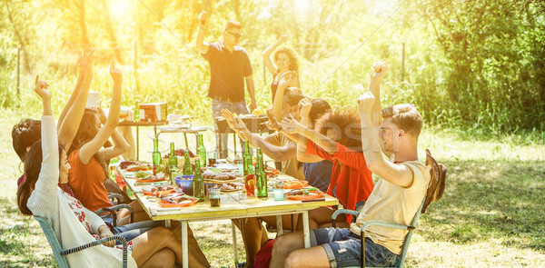 Stock photo: Happy friends having fun eating at barbecue party outdoor big ho