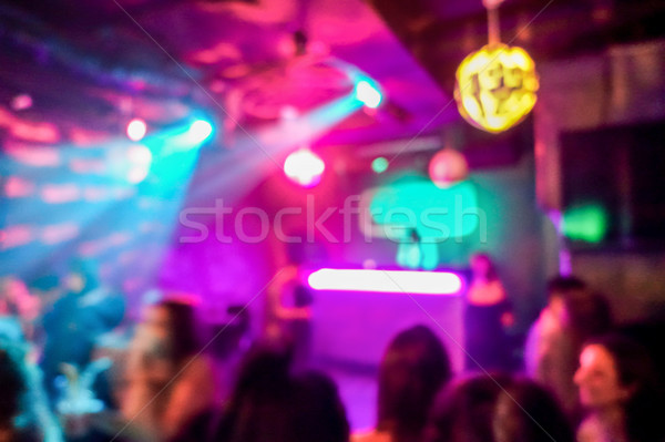 Blurred people inside disco club with colorful laser lights in b Stock photo © DisobeyArt