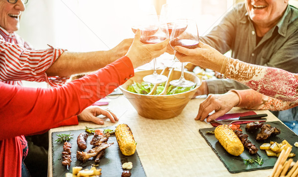 Stock photo: Senior friends cheering with red wine at barbecue lunch indoor -